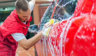 Male washer soaping the red car in car wash service.