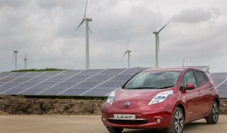 EV parked next to solar and wind farm